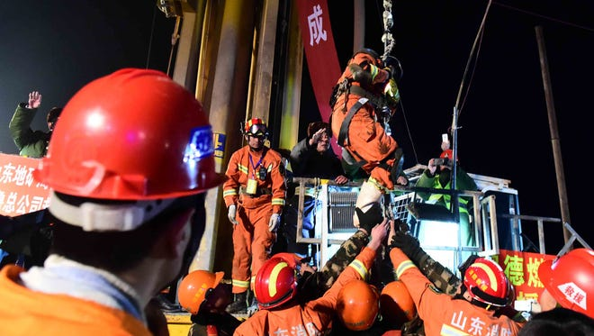 The first miner, center on hoist,  is lifted from a collapsed mine in Pingyi, east China's Shandong Province, Jan. 29, 2016 after 36 days underground.