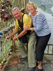 Emma and Mike Burns from Scottsdale celebrate their 50th anniversary on the Via dell'Amore trail in Riomaggiore, Italy by placing a padlock on the entrance to the famous trail.
