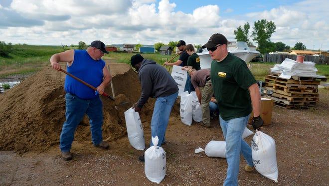 Volunteers fill sandbags at the Vaughn Volunteer Fire Department Wednesday morning.