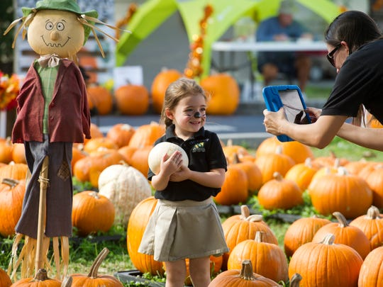 Addison Butz, 4, of Port St. Lucie, has her photo taken by Chesterbrook Academy Preschool teacher Laura Ward during a field trip to the pumpkin patch Oct. 18, 2016, at the First United Methodist Church in Port St. Lucie. It was the first church in Port St. Lucie, founded May 29, 1960.
