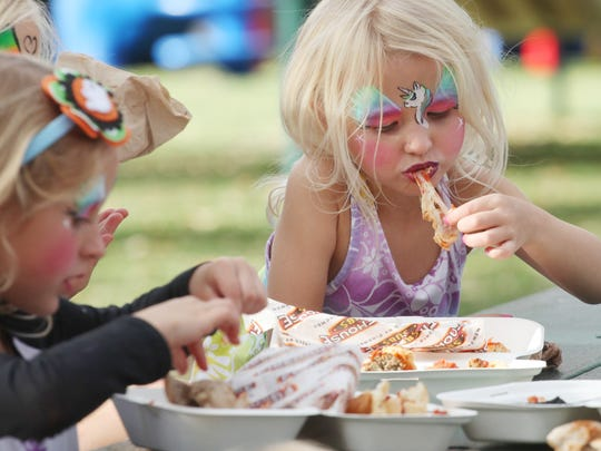 Lucy Perk, 3, munches on a sandwich from Firehouse Subs while attending Taste of the Cape.