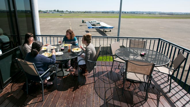 Diners eat lunch on the patio of Flight Deck Restaurant and Lounge with a view of the runway at McNary Field on Wednesday, April 6, 2016.