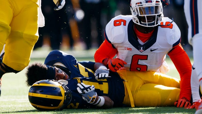 Michigan running back Chris Evans loses his helmet after getting tackled by Illinois defensive lineman Carroll Phillips (6) in the first half Oct. 22, 2016, at Michigan Stadium.