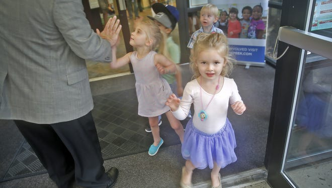 Preschool children welcome visitors with high fives to Day Early Learning Lilly Family Center, Friday, August 12, 2016.