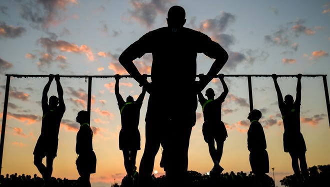 """A drill instructor watches as new male recruits do two complete """"dead-hang"""" pull-ups during their Initial Strength Tests (ISTs) on Thursday October 20, 2016 at the Marine Corps Recruit Depot in Parris Island, SC. In order to begin boot camp in earnest, new recruits must be able to do two complete """"dead-hang"""" pull ups, 44 crunches in two minutes and a one mile and half run in 13 minutes and 30 seconds."""