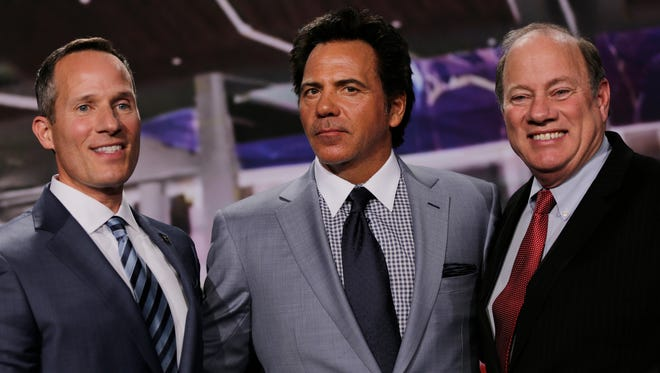 Christopher Ilitch, President and CEO, Ilitch Holdings, left, Tom Gores, Chairman and CEO, Platinum Equity and owner of Detroit Pistons and Detroit Mayor Mike Duggan pose after a press conference announcing the move of the Detroit Pistons to the Little Caesars Arena in Detroit on Nov. 22, 2016.