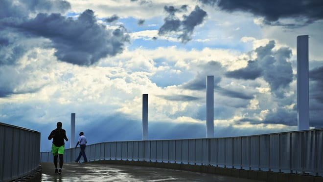 A jogger and walker make their way along the ramp of the Big Four Bridge Wednesday morning as clouds roll overhead. A jogger and walker make their way along the ramp of the Big Four Bridge Wednesday morning as clouds roll overhead.