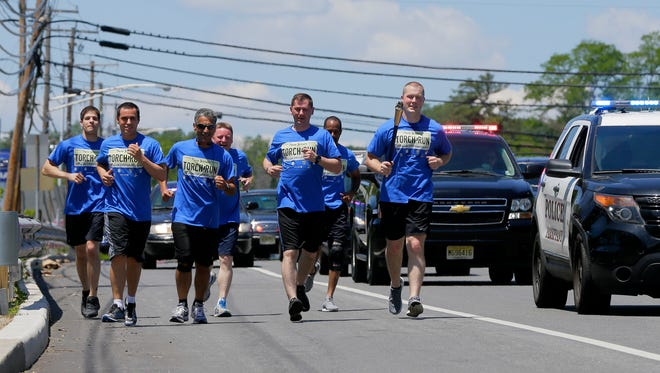 Members of the Parsippany Police Department run along Route 46 from Mountain Lakes to the Smith Field Park in Parsippany during the Law Enforcement Torch Run for Special Olympics from Mountain Lakes to Parsippany, NJ Friday, June 9, 2017.