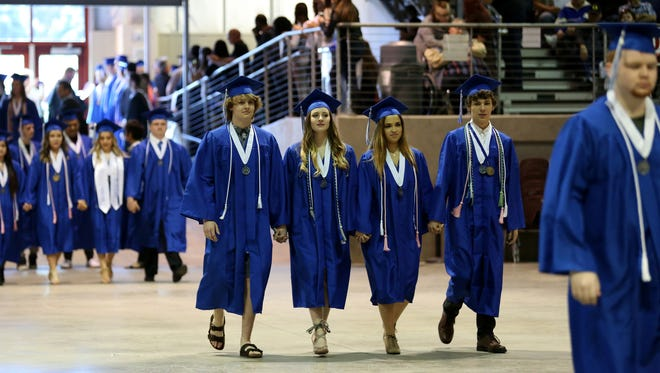 Graduates enter the arena during the McNary High School commencement at the Oregon State Fairgrounds Pavilion on Friday, June 9, 2017.