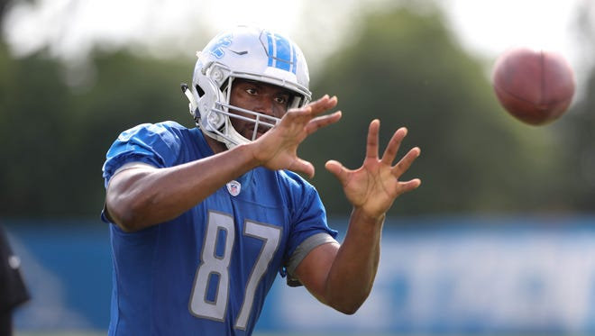 Lions tight end Darren Fells catches balls from a passing machine during practice Sunday, July 30, 2017 in Allen Park.