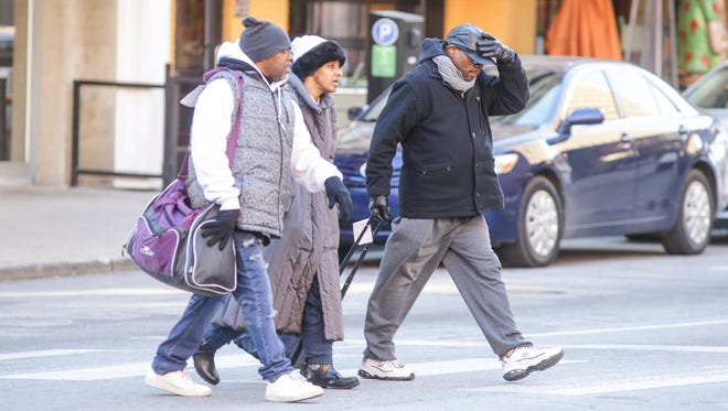 A group bundles up for the cold while walking in Downtown Indianapolis.