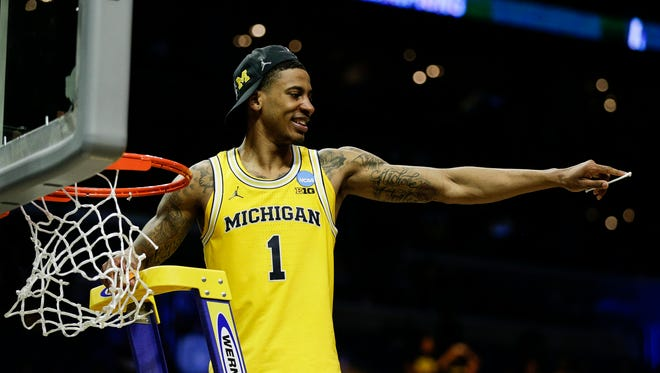 Charles Matthews celebrates the cutting of the net after Michigan defeated Florida State, 58-54, on Saturday.