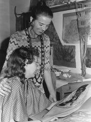 Art teacher Martha Kiel, standing, admires the wearable