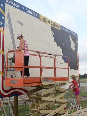 Dover artist Sarah Dugger and her daughter Teagan work on the John Glenn mural at Harry Clever Field on Thursday. The late U.S. senator and astronaut learned to fly at the airport. Clever was his instructor. The art project is made possible through charitable donations from AquaBlue, Inc., and the Regina Whittingham Trust.