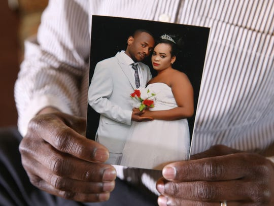 Sudanese refugee Al Ghali Yahia holds his wedding photo