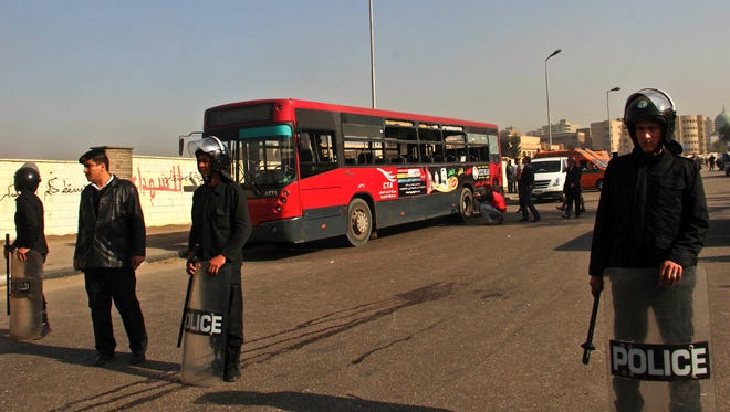 Egyptian policemen stand guard after an explosion has hit a public bus, background, in Cairo's eastern Nasr City district Thursday.