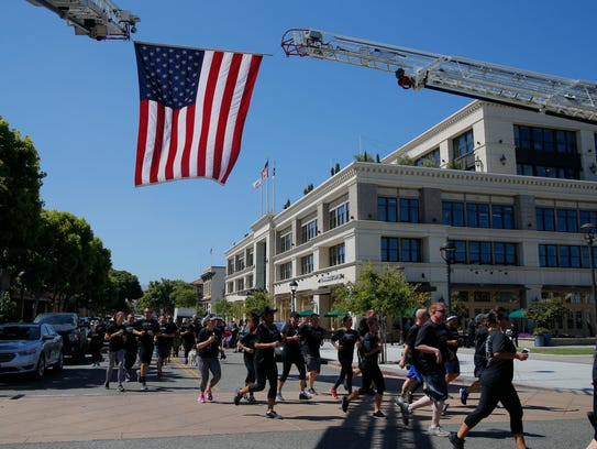 Runners pass under a flag held up by the Salinas fire