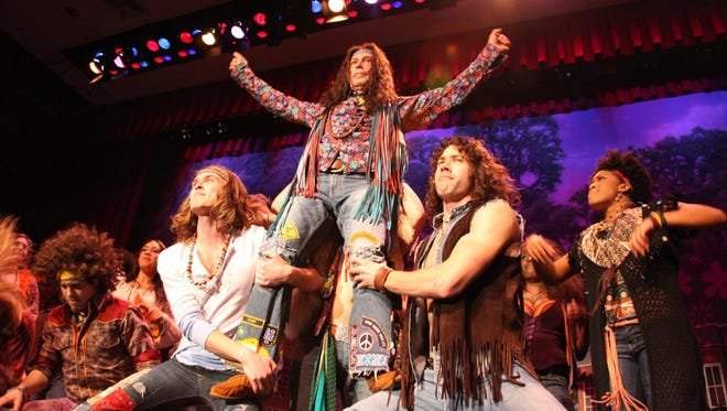 """Then-New York City Mayor Michael Bloomberg, center, performs with the cast of the musical """"Hair"""" in 2010."""