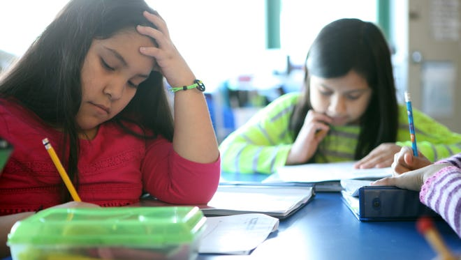 Third-graders Karina Mojica and Mishelle Espinoza solve math problems in the English side of an English/Spanish bilingual class on Jan. 28 at Alice E. Grady Elementary School. New York's Common Core test-scoring scales were set last summer by 95 educators the state gathered at a Troy hotel for several days.