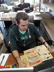 Brian Leary looks through a Jetson's comic to determine the value of the book on Feb. 17, 2015 at NewKadia comics in Norristown, Pa. They use 7 different criteria to break down the comics worth.