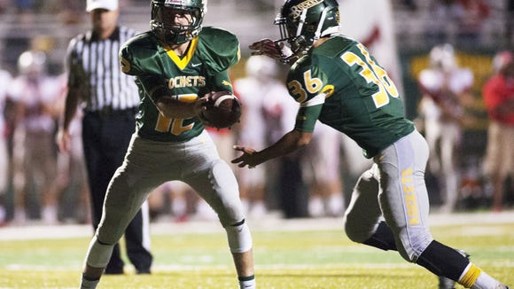 Reynolds quarterback Nathan St. Onge hands the ball off to Darien Caldwell in the second half of Friday's home win over Hendersonville.