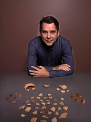 Tom Garner with assorted pottery sherds he originally found on the surface of the Luna settlement, including Spanish olive jar, lead glazed coarse earthenware, majolica, and incised and plain Native American pottery.
