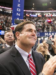 Gov. Doug Ducey (foreground) and Robert Graham, chairman of the Arizona Republican Party, celebrate after it was announced Donald Trump had won their party's nomination for president at the GOP National Convention at QuickenLoans Arena in Cleveland.