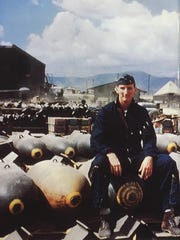 Bob Gilliland sits on 1,000-pound bombs at K-2 Airport in Taegu, Korea in 1952 when he was a fighter-bomber pilot flying the F-84 Thunderjet.