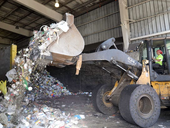 A front end loader dumps recyclables into a conveyor
