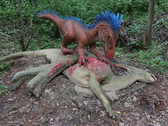 A Deinonychus is seen with his prey in the forest.