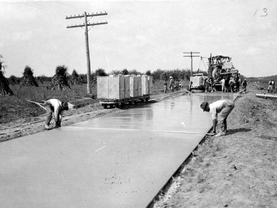 Workers pave a portion of DuPont Highway.