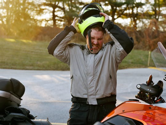 Judd Hill removes his motorcycle helmet after arriving for work at YTI Career Institute's Motorcycle Technology Center Thursday, Dec. 21, 2017, in Manchester Township.