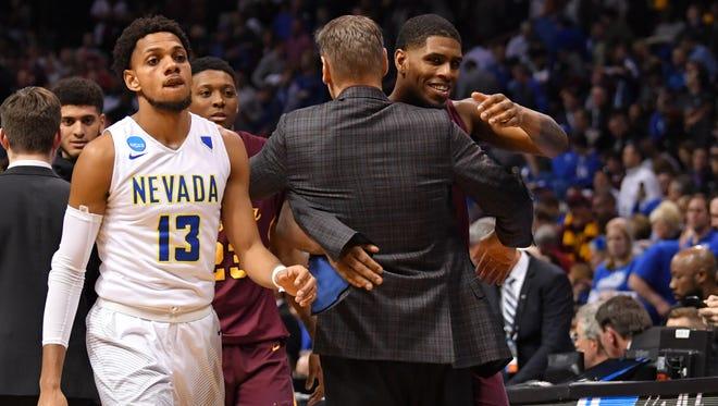 Loyola's Aundre Jackson (24) hugs head coach Porter Moser after the Ramblers beat Nevada on Thursday.