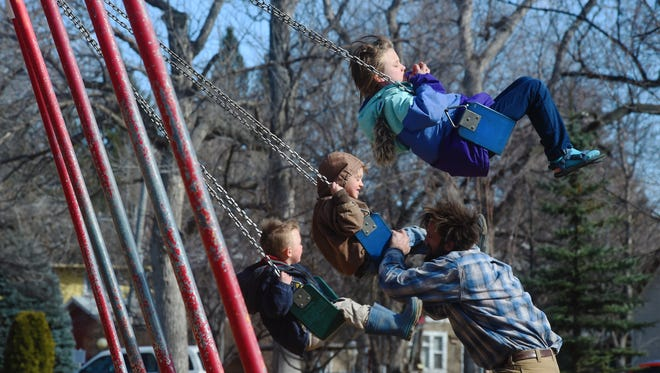 Saxon Polich and his kids: Ellis, age 3, left; Thurston, age 5, center; and Ayla, age 7; play on the swing set at Gibson Park on Monday afternoon.