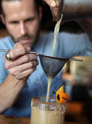 """James Downs, a bartender at Selden Standard prepares a cocktail called  """"The Burden of the Sea Captain."""" He will be participating in the 2nd Annual Detroit Cocktail Classic Saturday, Oct. 3, 2015, at the Garden Theater in Midtown Detroit from 7 p.m.-11 p.m."""