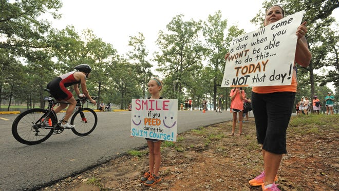 D'Ann Gerbine and her daughter Brynn Gerbine try to bring a smile to the competitors at the 2014 Sportspectrum River Cities Triathlon held Sunday  at the Cypress Lake Park near Benton.