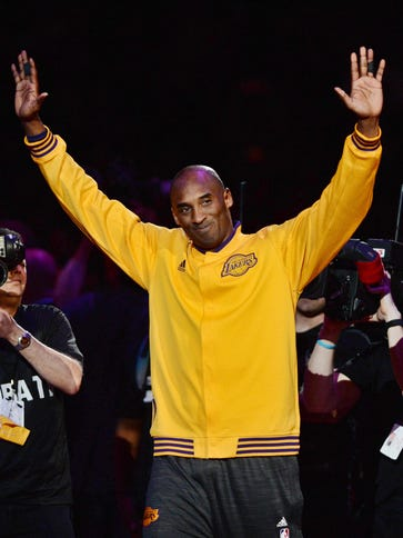 Kobe Bryant waves to the crowd as he walks on the court