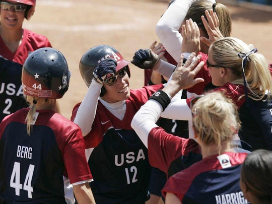 Team USA's Kelly Kretschman (12) is mobbed by teammates after she hit a home run in the 2004 Olympics.