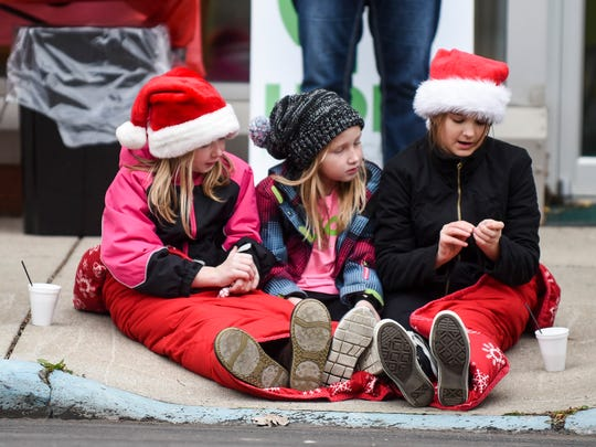 Children dressed for the cold, and for the holiday, wait patiently on the curb of Center Street for the Christmas Parade to begin on Saturday afternoon.