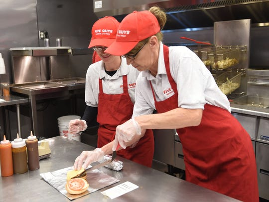 Five Guys general manager Chaz Ashley, left, and employee