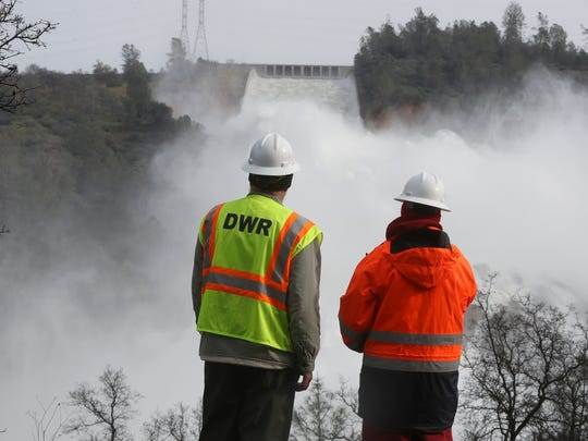California Department of Water Resources workers watch water pour down the Oroville Dam spillway as authorities try to reduce the amount of water in the lake in preparation of coming storms and to be able to make repairs to the damaged spillway.
