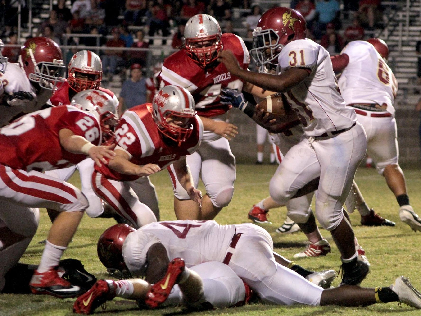 Humboldt's Jaylon Stewart (31) attempts to break tackles while rushing the ball against McKenzie last season.
