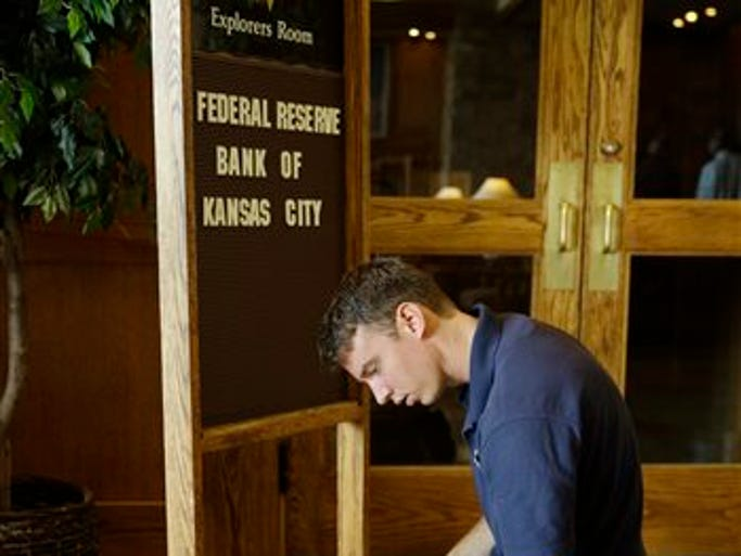 Tyler Lovelady puts letters on a sign in preparation for the Jackson Hole Economic Policy Symposium at the Jackson Lake Lodge in Grand Teton National Park near Jackson, Wyo., Thursday, Aug. 21, 2014. The Federal Reserve Bank of Kansas City is holding the Jackson Hole Economic Policy Symposium at the hotel. The central bankers meeting this week at their annual conference in Jackson Hole, Wyoming, aren't exactly in sync. Many are taking steps that clash with the policies of others. The Federal Reserve is preparing to reduce its economic support. By contrast, the European Central Bank is considering more stimulus. So is the Bank of Japan. The Bank of England seems to be moving toward raising interest rates.