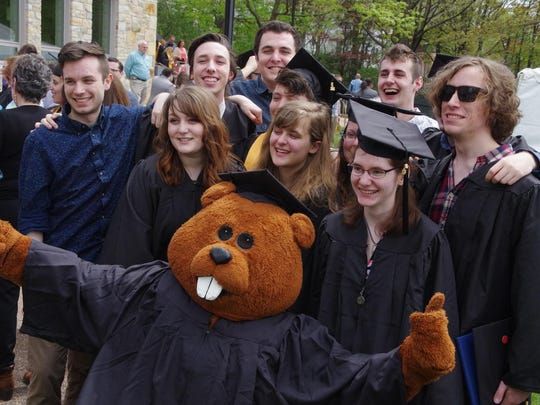 Champlain College Mascot Chauncey T. Beaver poses with a group of gradutes at the reception.
