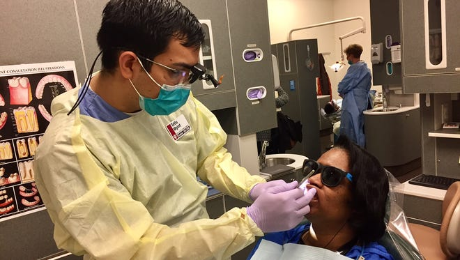 Third-year dental student Tetlu Myint examines Bertha Sanders at the IU Dental School Outreach Clinic on the east side.