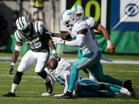 New York Jets' Elijah McGuire (25) fumbles after Miami Dolphins' Byron Maxwell (41) stripped the ball during the second half of an NFL football game Sunday, Sept. 24, 2017, in East Rutherford, N.J. The Dolphins recovered the ball on the play. (AP Photo/Seth Wenig)