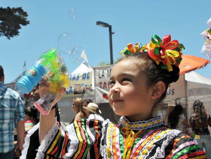 Litzy Martinez, 5, blows bubbles for a fan at Sunday's 20th annual Viva la Familia concert event at the Salinas Sports Complex.