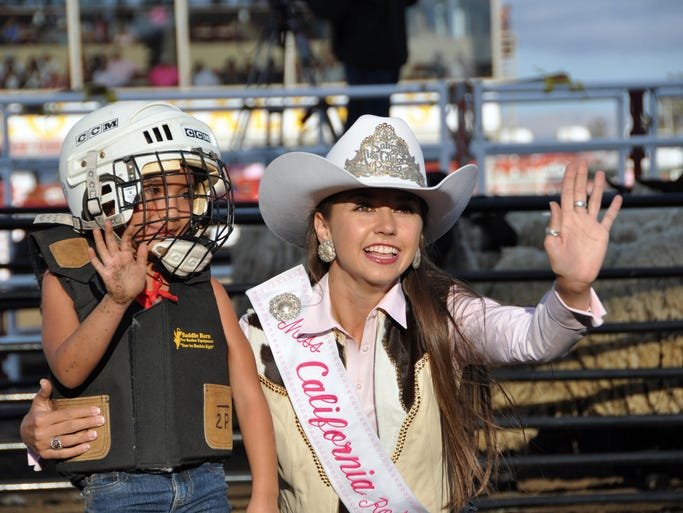 "Grace Tobias, right, helps a somewhat dazed Alexa Garcia wave to the crowd after her ride on a sheep at Thursday's ""Tough Enough To Wear Pink"" night at the 2014 California Rodeo Salinas."