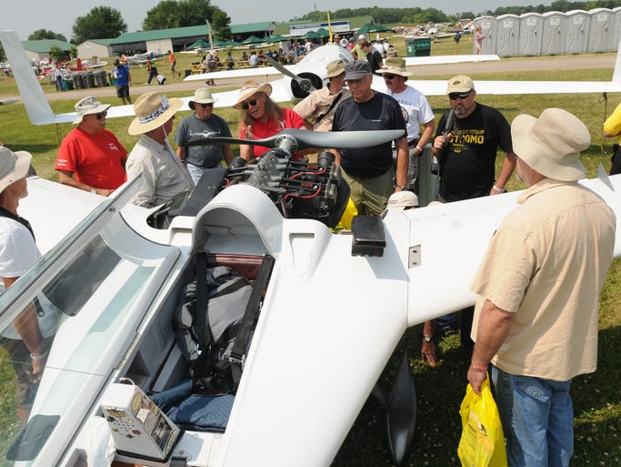 Bill James talks about his Vari Eze  with Christine Bush and others gathered around the plane on the fourth day at AirVenture 2014.