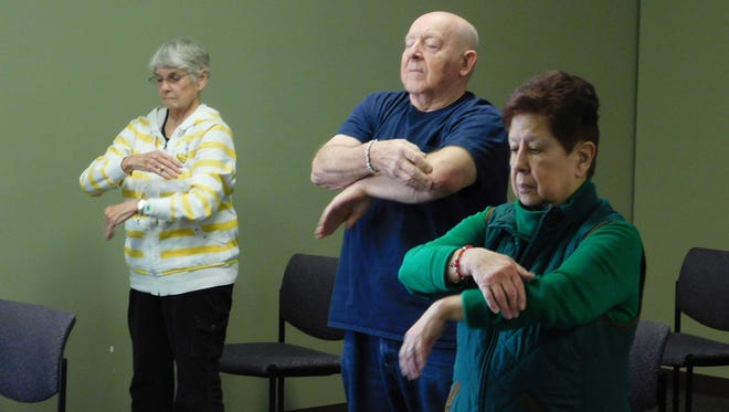 Marilyn Sweet, Rod Wilbur, and Agatha Snoep (from left) participate in a Tai Chi class as part of the Cancer Survivors Fitness Program at McLaren Greater Lansing.